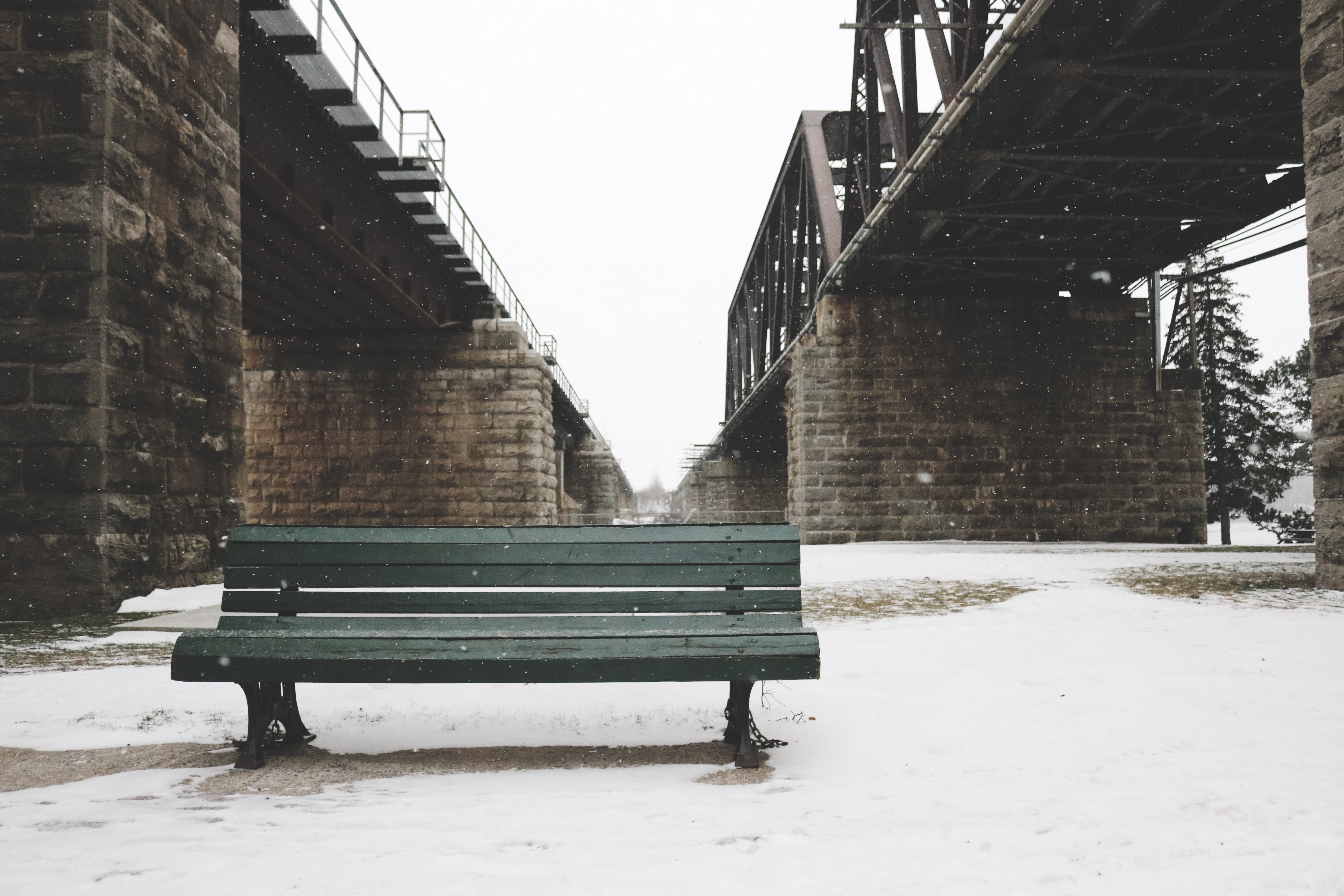 A green wooden bench sits below and between two bridges during a snowfall