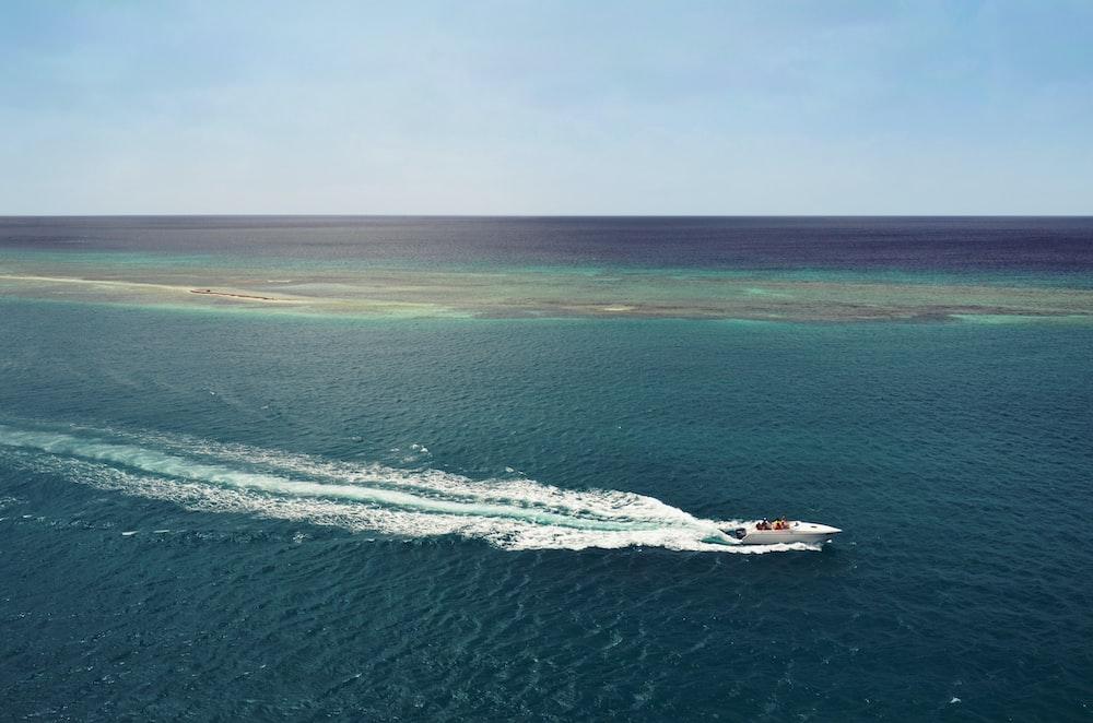 white speedboat running in middle of ocean during daytime