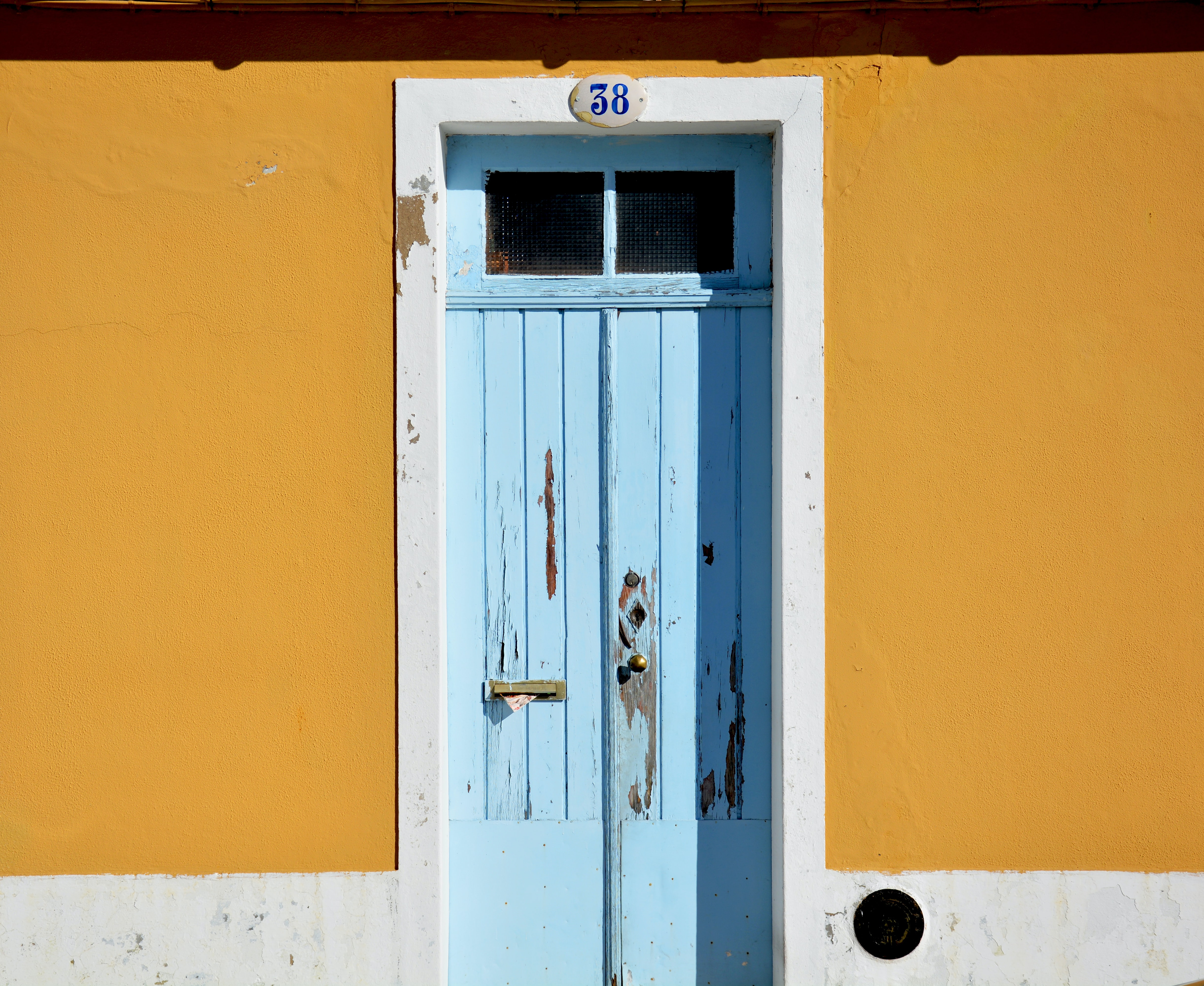 Old wooden door with chipped blue paint with a brass doorknob and the number 38 at the top surrounded by mustard yellow walls