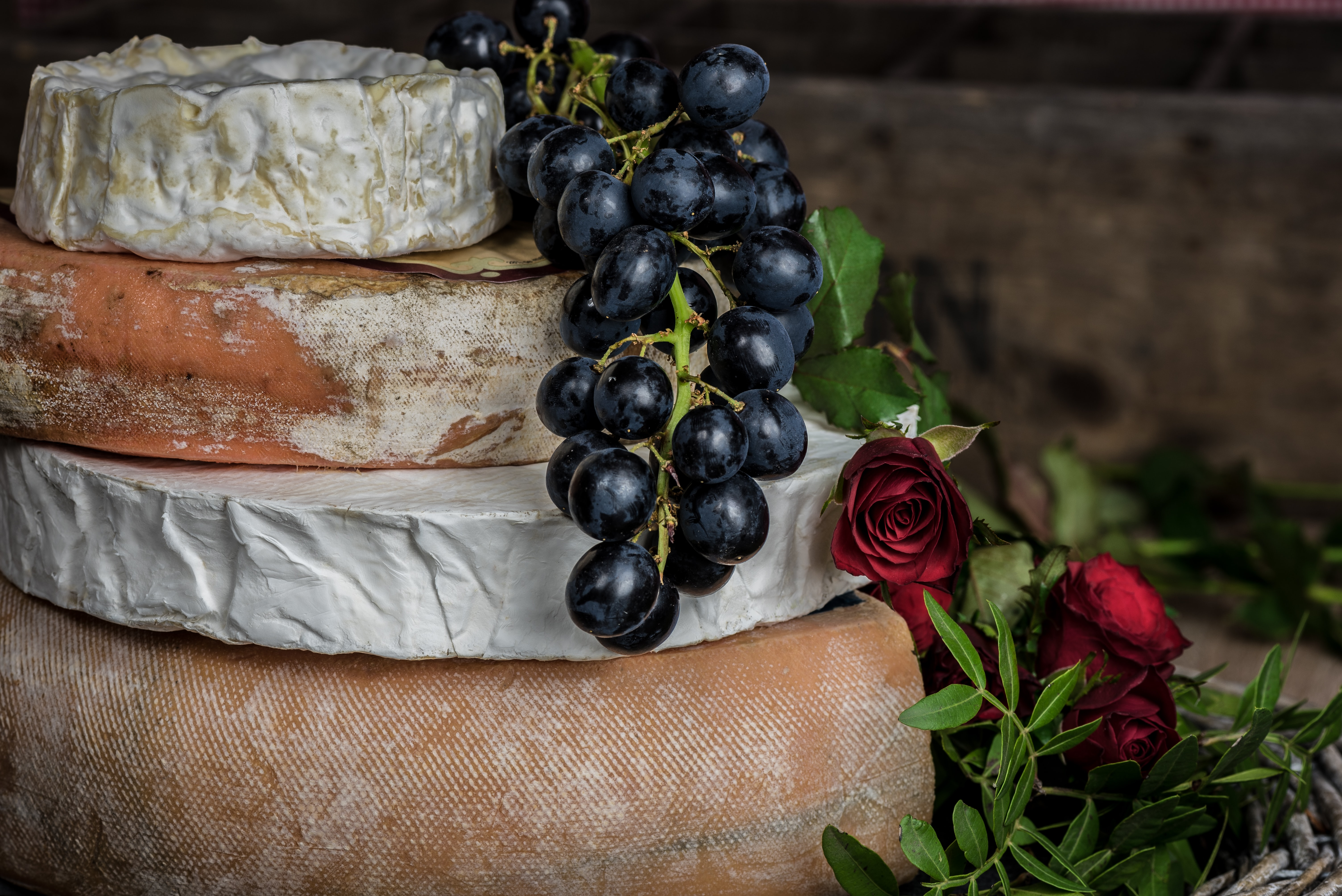 Stack of camembert, brie, and assorted gourmet cheeses with grapes and roses