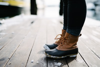 person wearing brown-and-black leather duck boots standing on brown wooden dock chilly teams background
