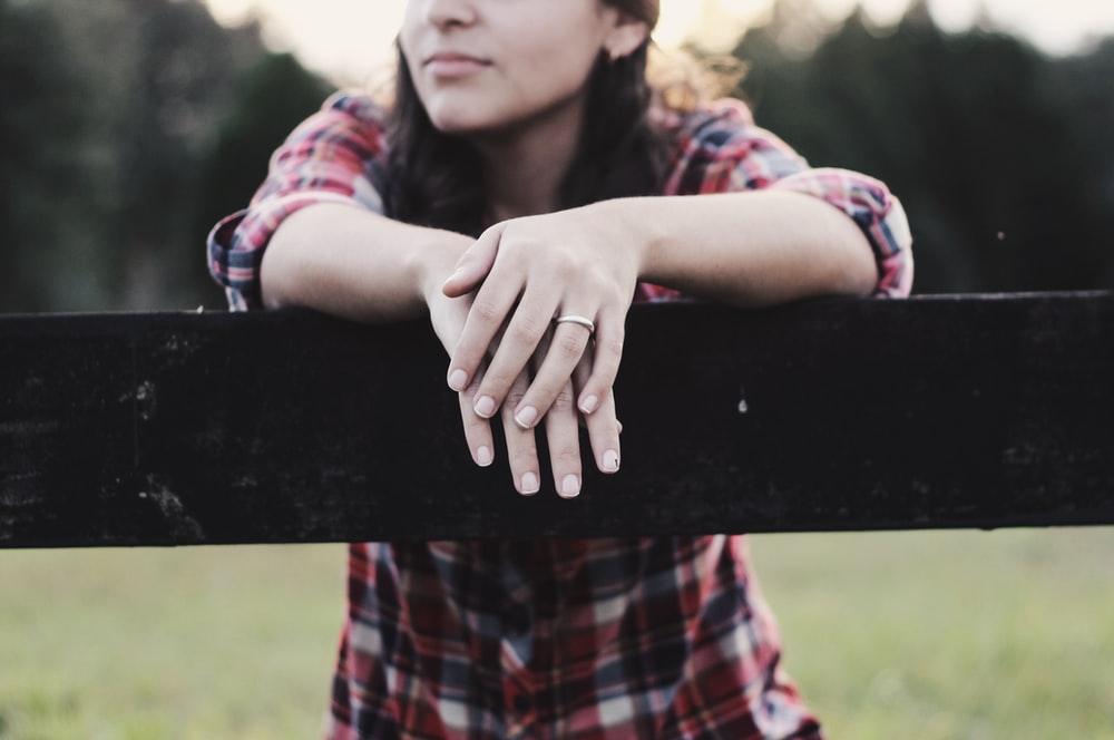 Woman wearing flannel stands over wooden post with dark lighting