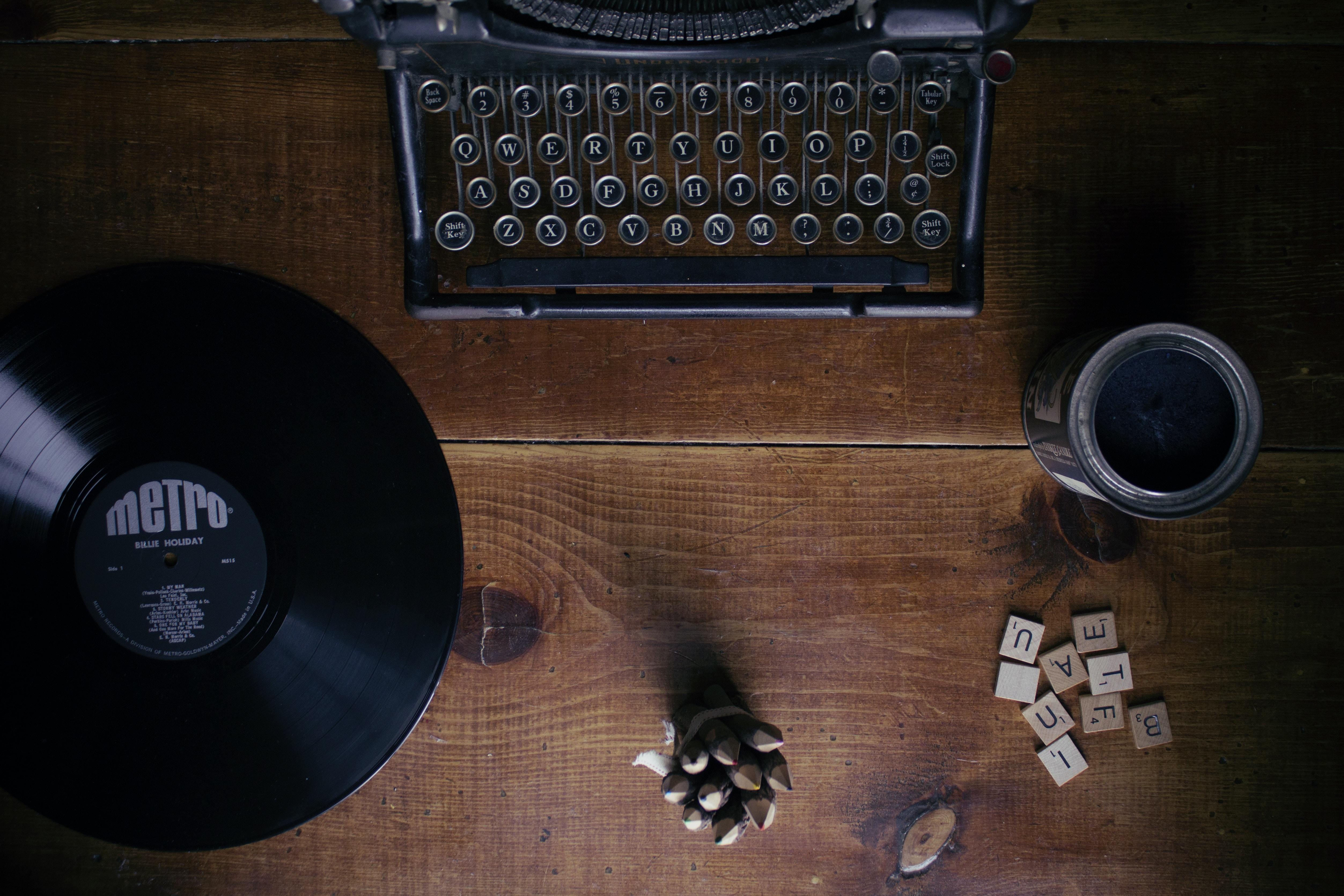 black typewriter beside black Metro vinyl record