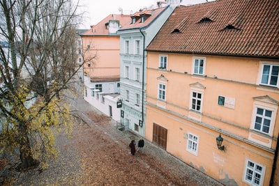 man and woman walking outside the 3-storey house near green tree photo during daytime prague teams background