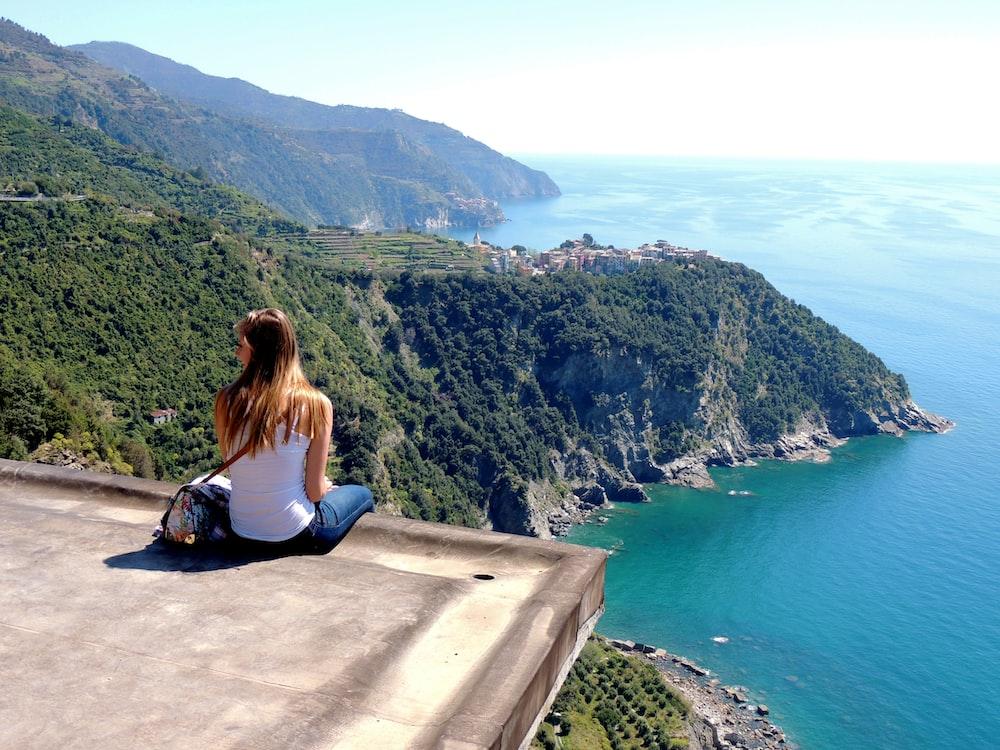 woman sitting on the edge of concrete block facing coast