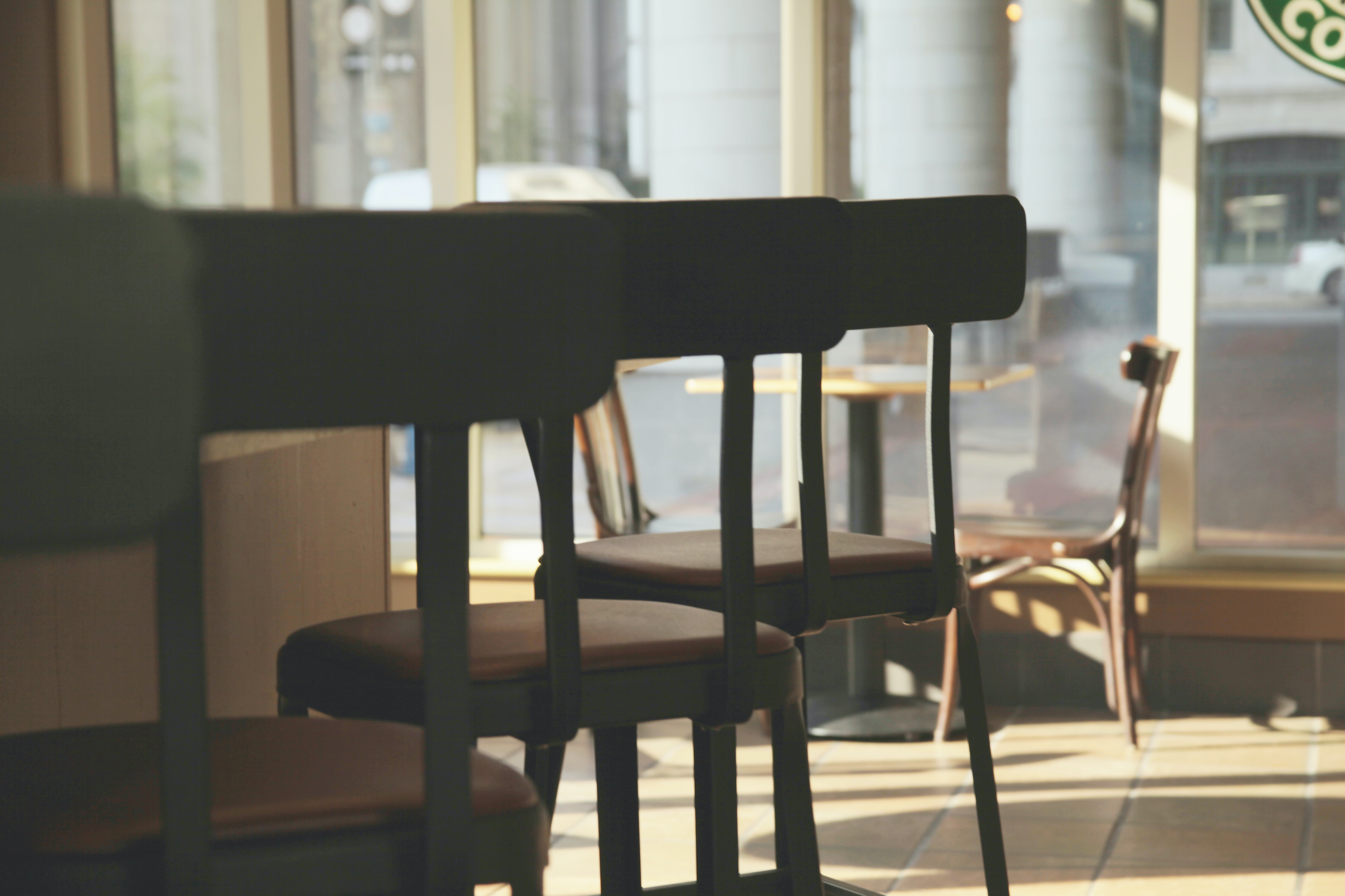 silhouette photography of gray bar stools placed at side of bar counter in a dim-lit store