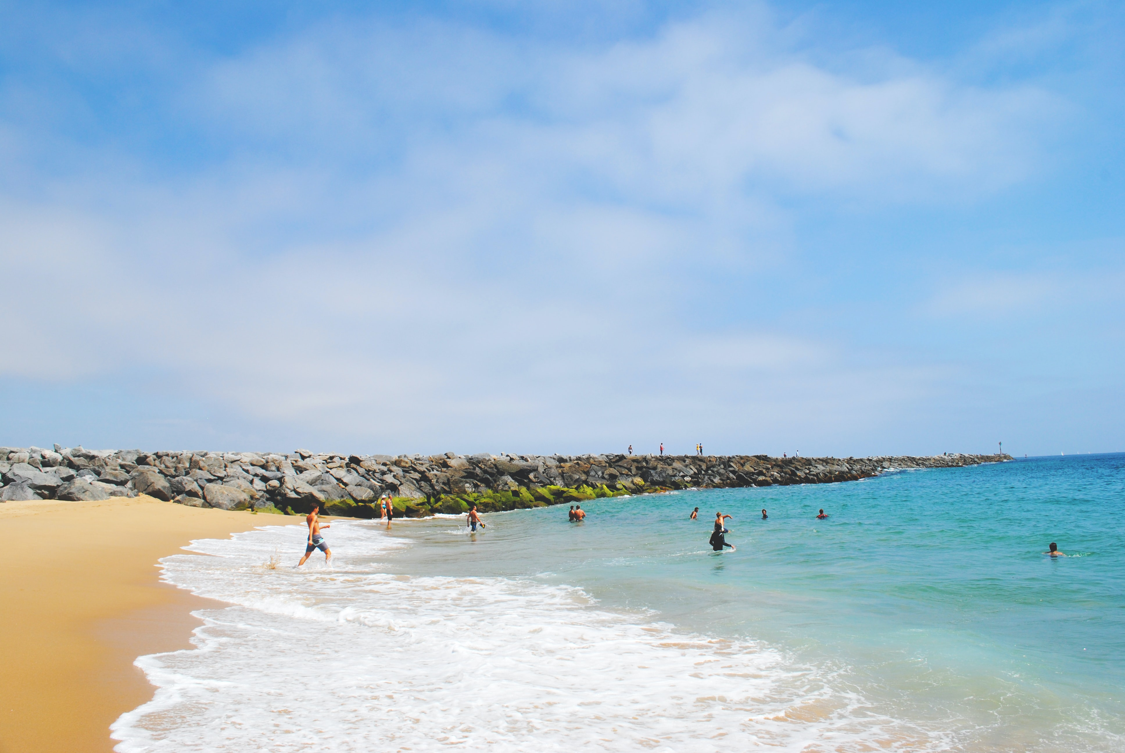 People enjoying and swimming in the ocean with side rocks during summer holiday in Newport Beach
