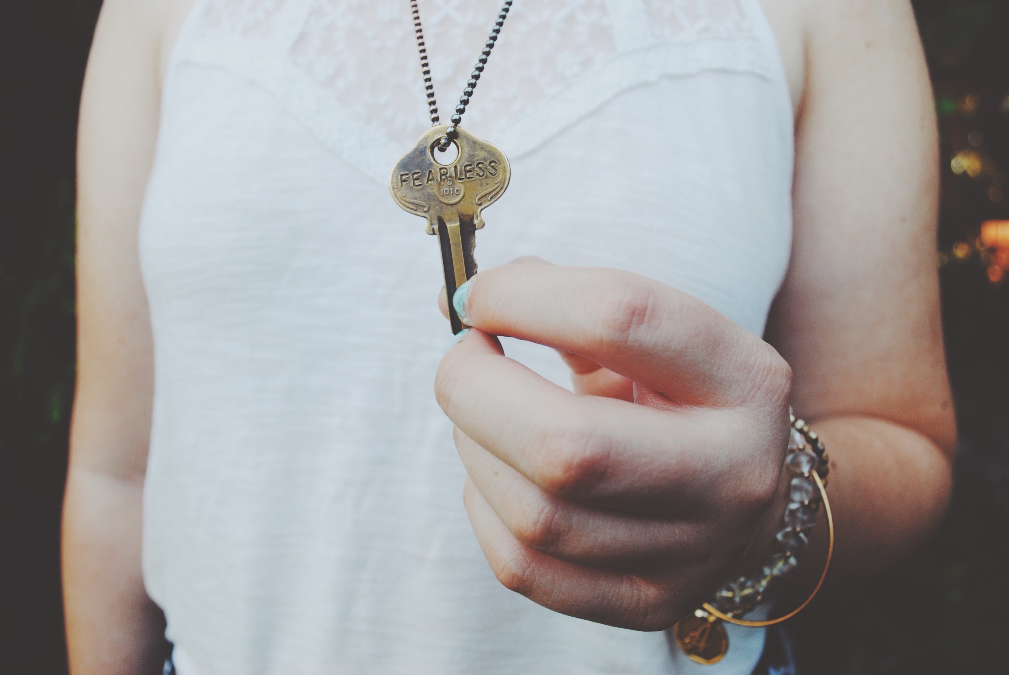 "A person holding a key with the word ""fearless"" etched on it"