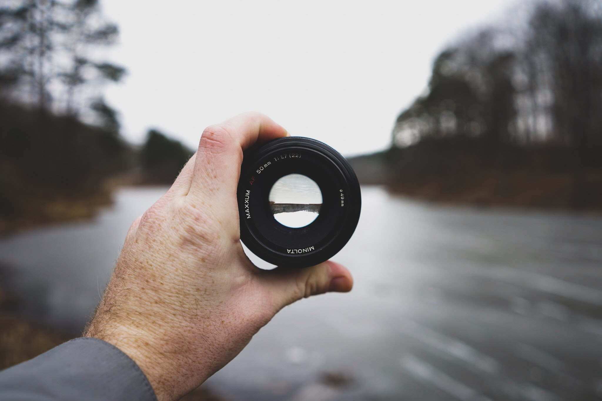 selective focus photo of person's hand holding black camera lens