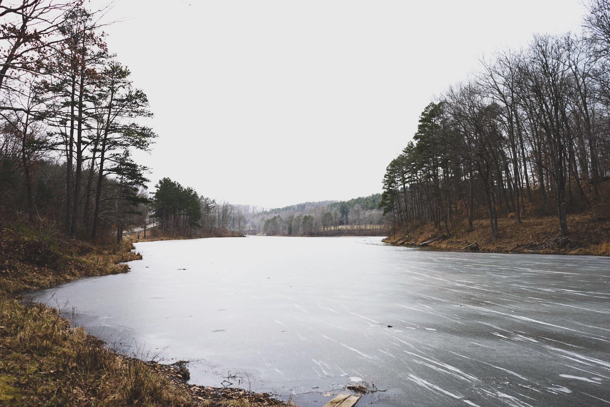 A small frozen lake under pale white sky
