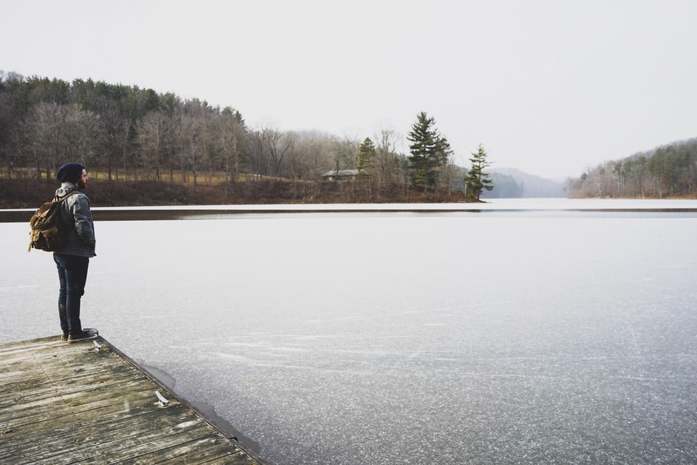 woman standing in front of lake while staring at it