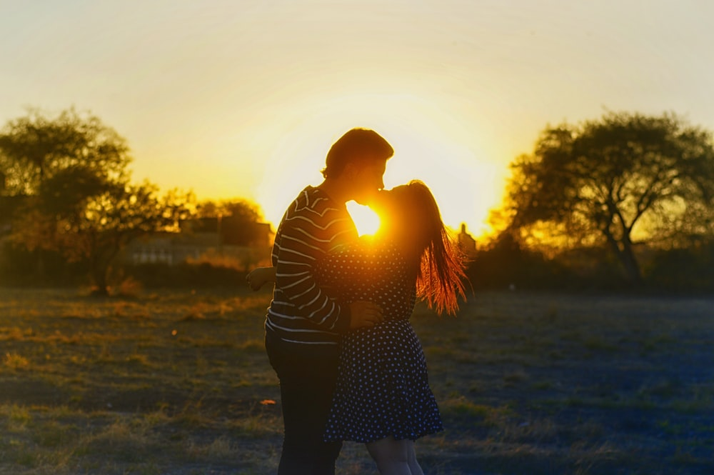 silhouette photography of couple kissing in the middle of the field