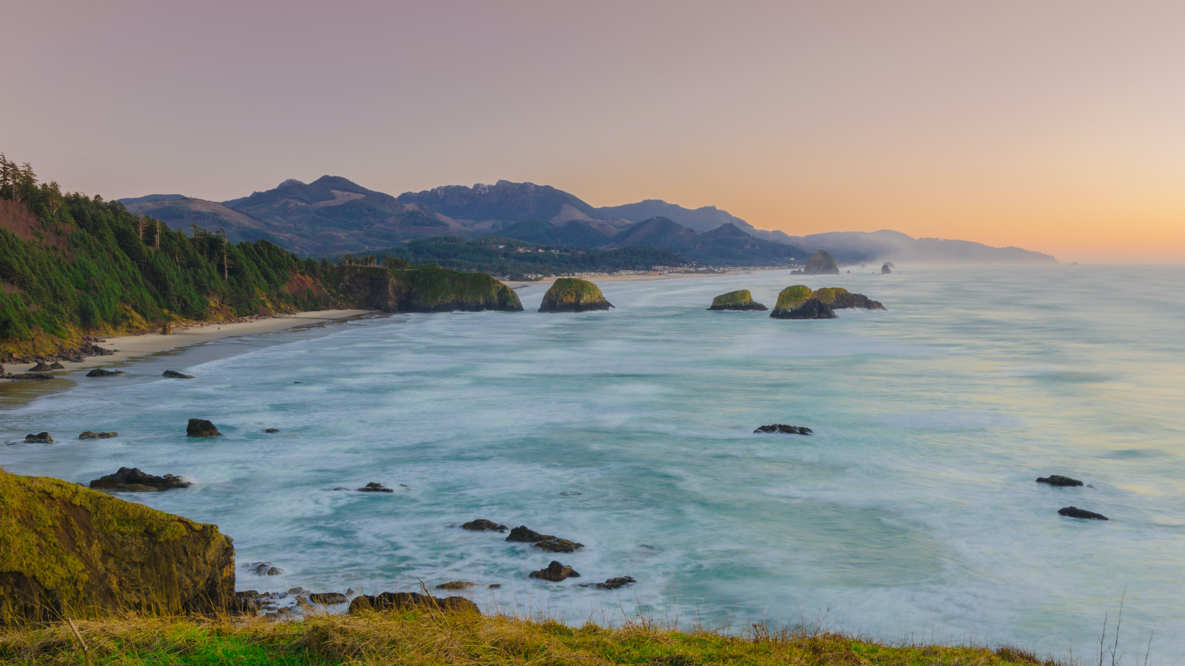 Ocean washing on a sandy beach with green cliffs in Ecola State Park at sunset