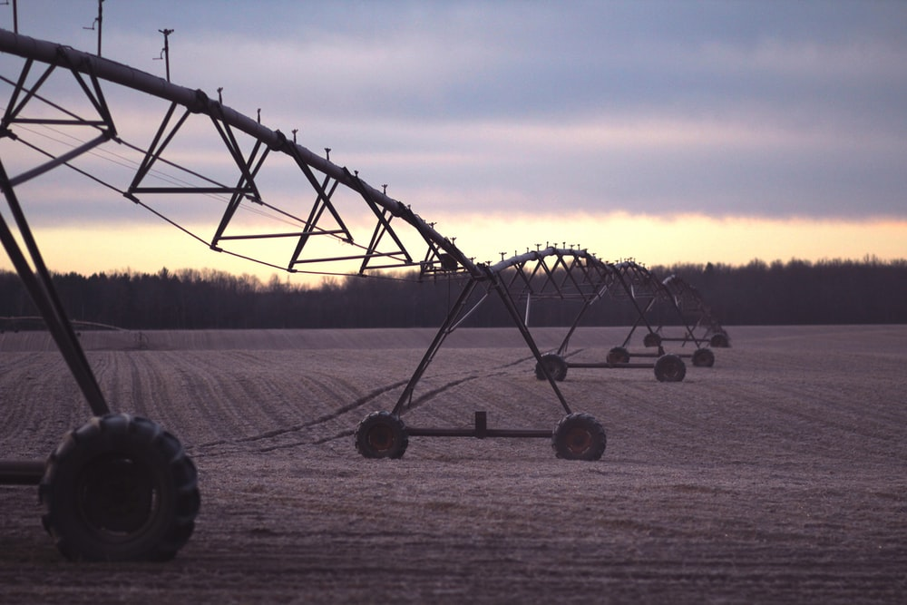 photo of black farming equipment under white clouds at daytime