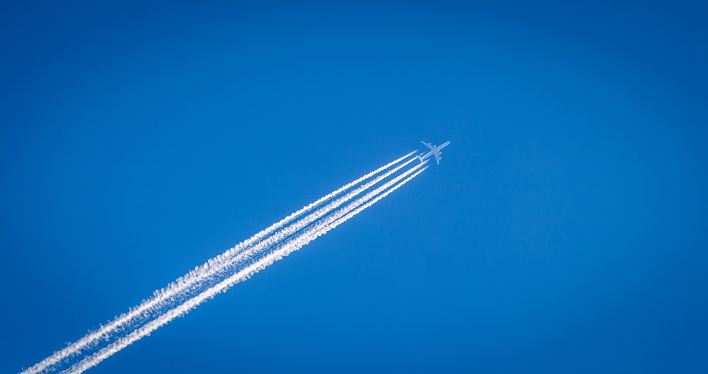 white airplane flying under the blue sky