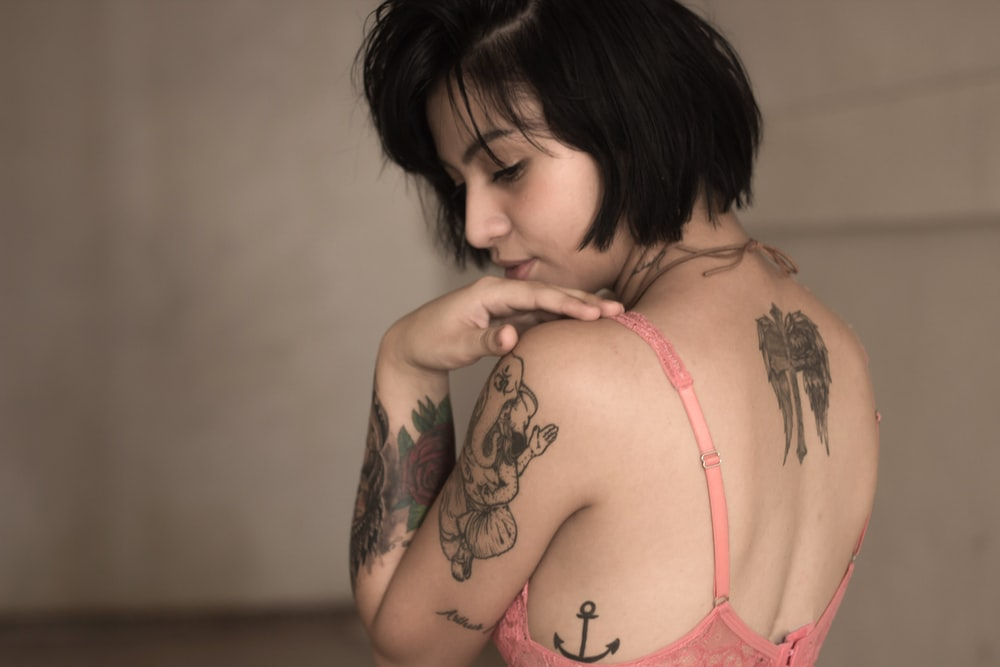 Woman with edgy tattoos and short bob looking over her shoulder