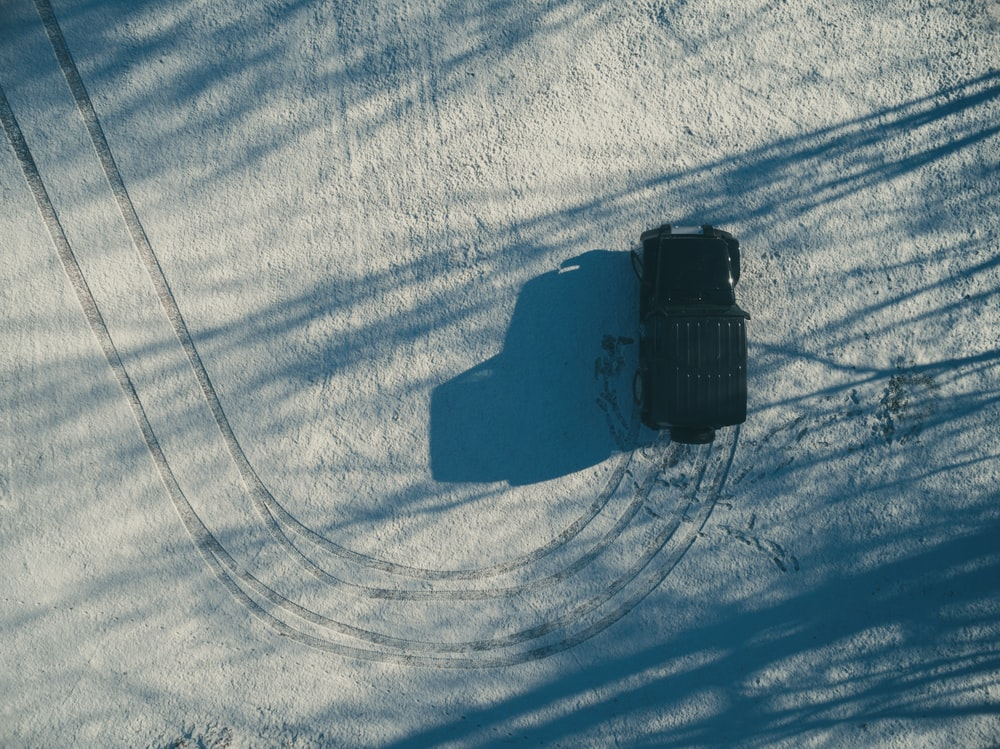 aerial photography of black SUV on dirt road at daytime