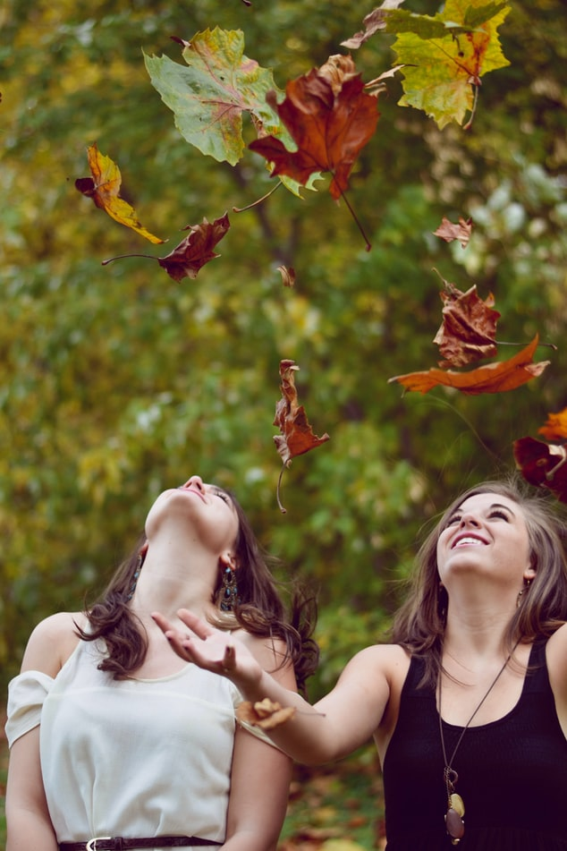 photo of two women throwing leaves during daytime