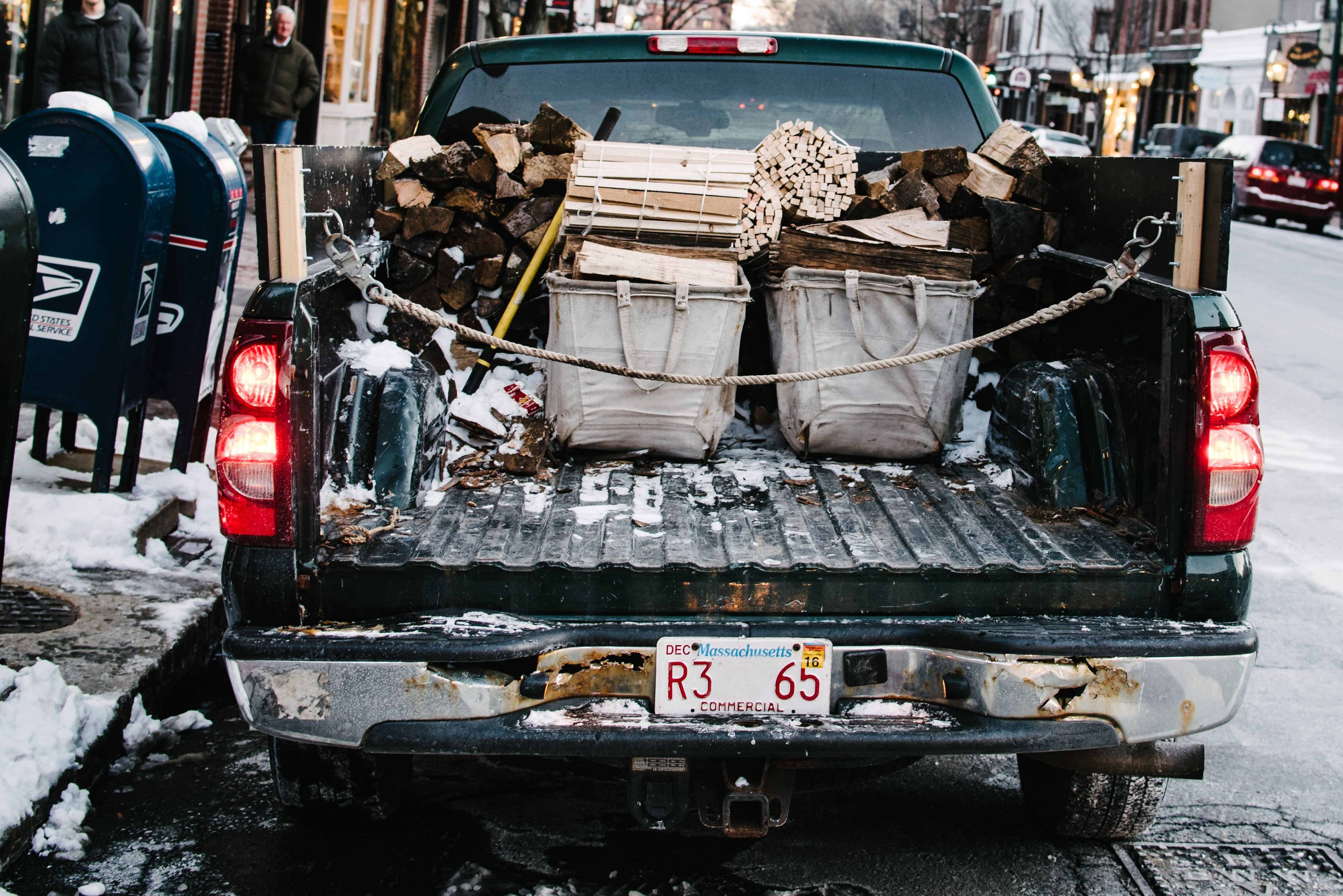Open flatbed of a truck in Boston winter containing chopped wood and storage baskets