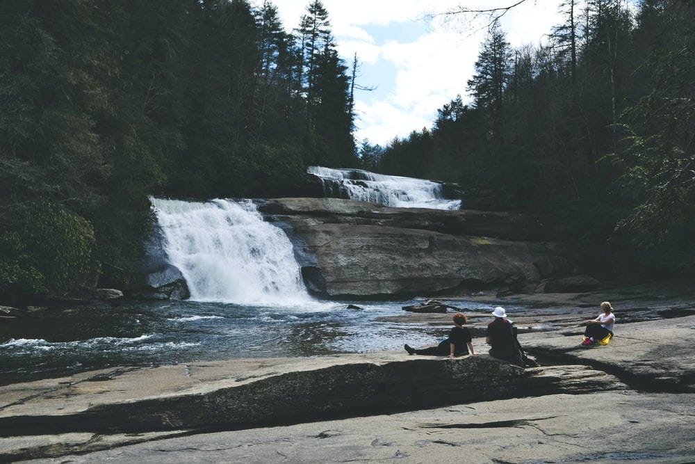 three people sitting on gray surface in front of waterfall