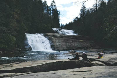 three people sitting on gray surface in front of waterfall north carolina teams background