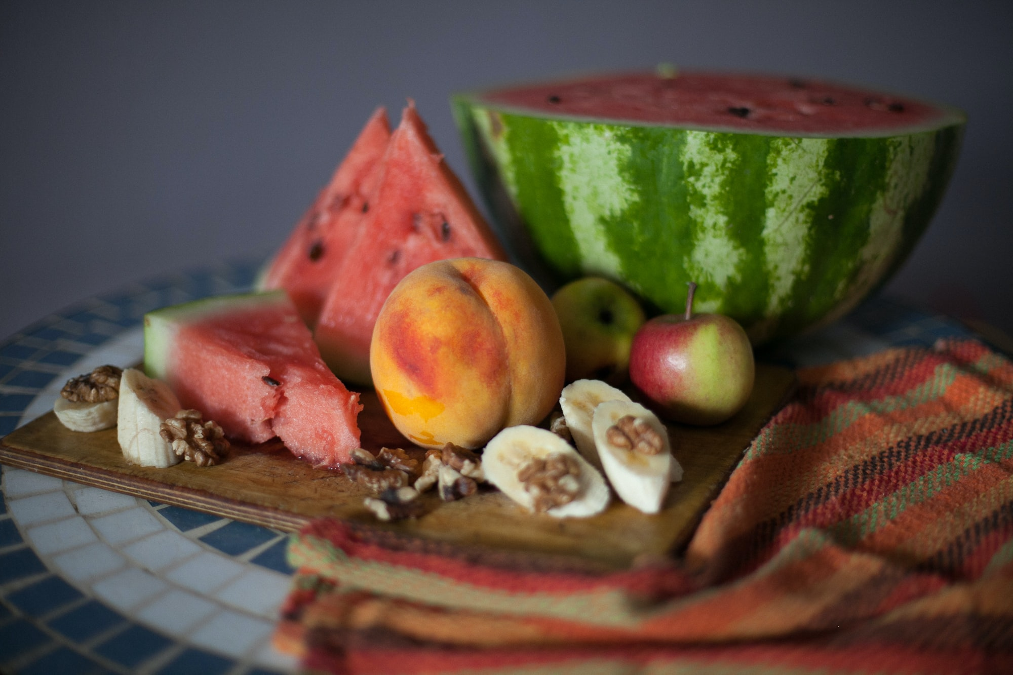Sliced watermelon, banana, peaches, fruit, and nuts on a cutting board