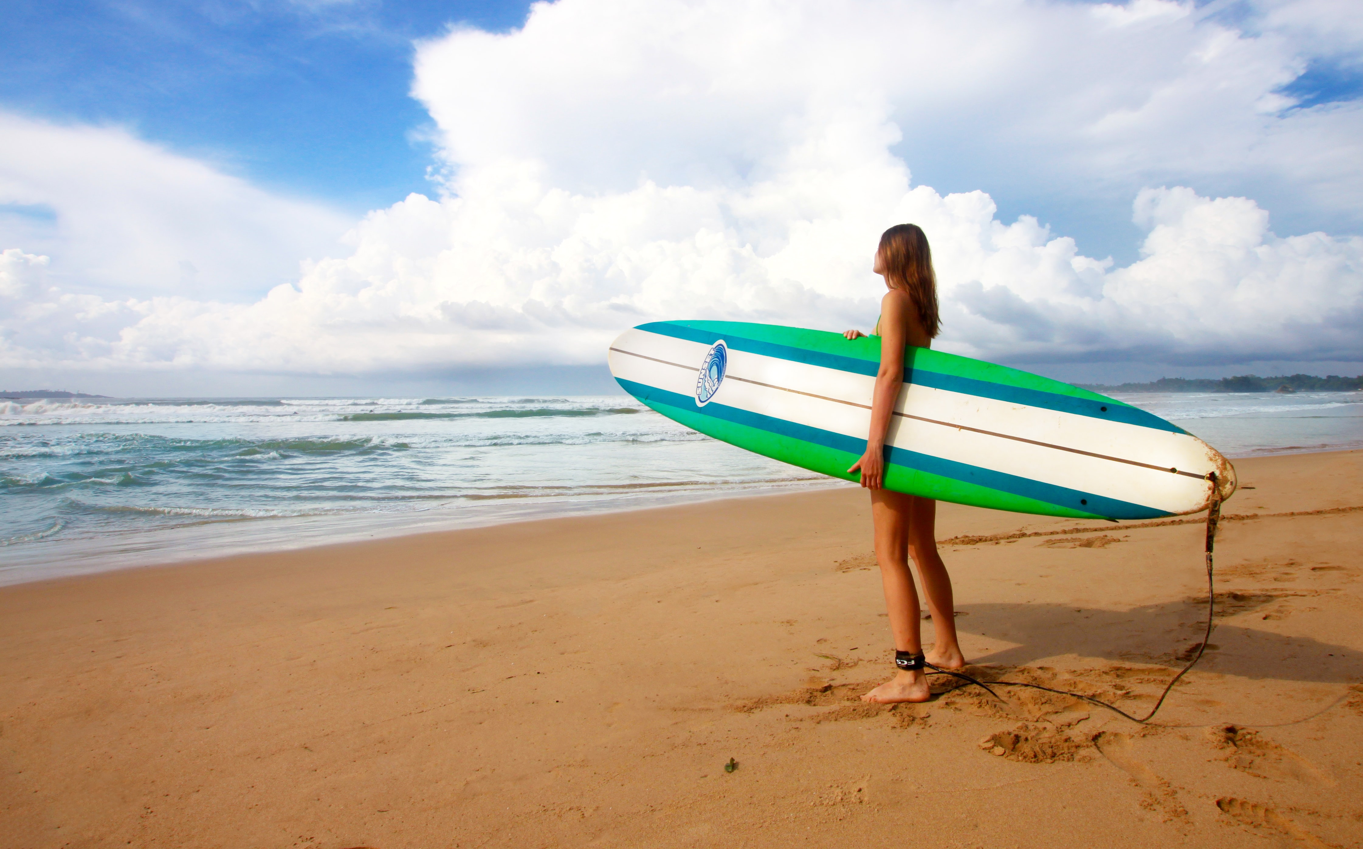 woman standing near sea holding white, blue, and green surfboard under blue sky