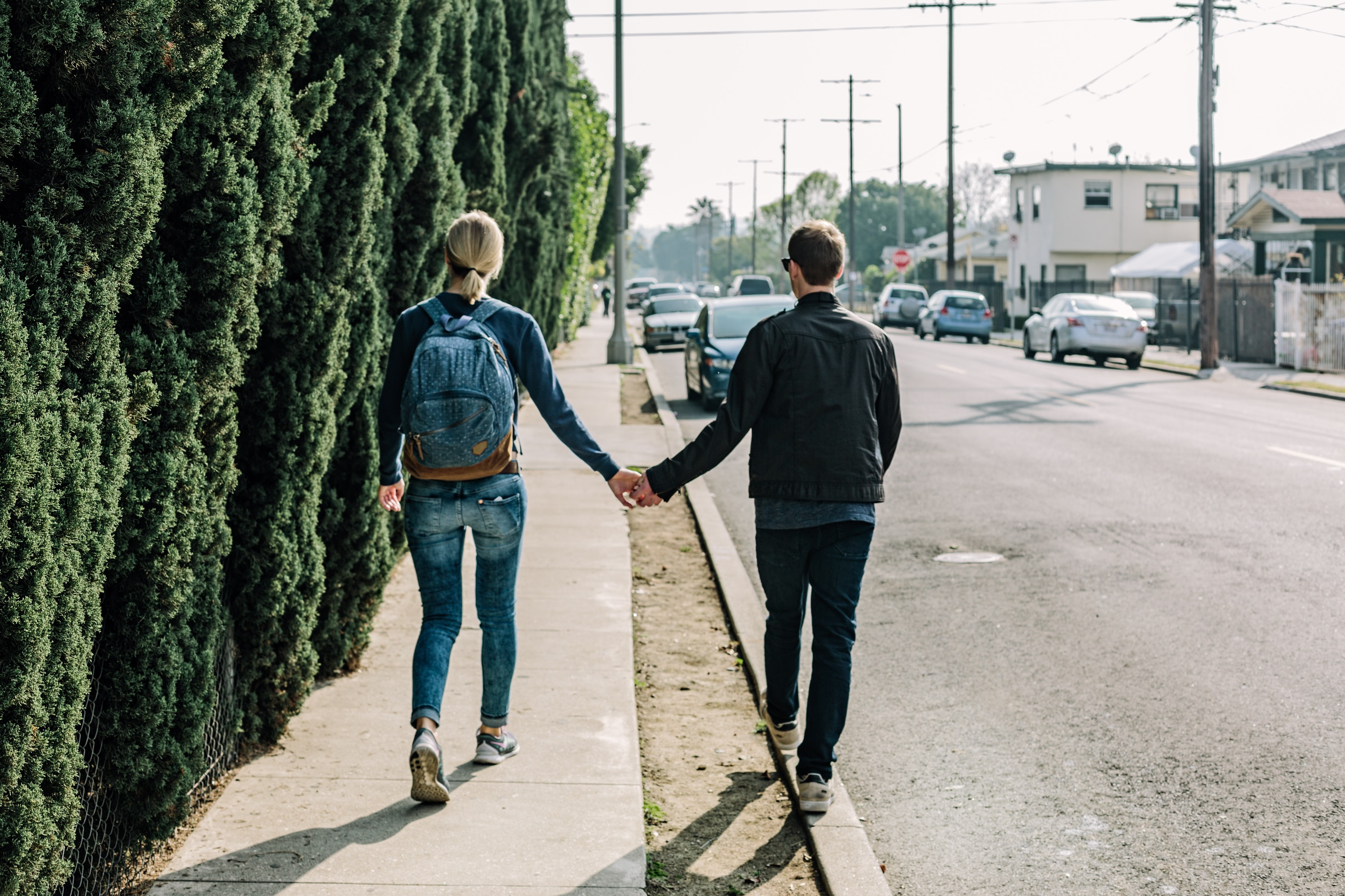 A couple walks holding hands, one on the sidewalk and one on the curb