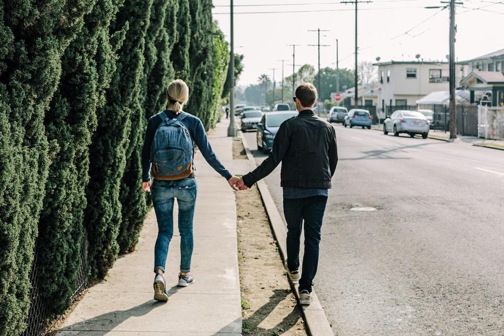 man and woman walking on pathway during daytime