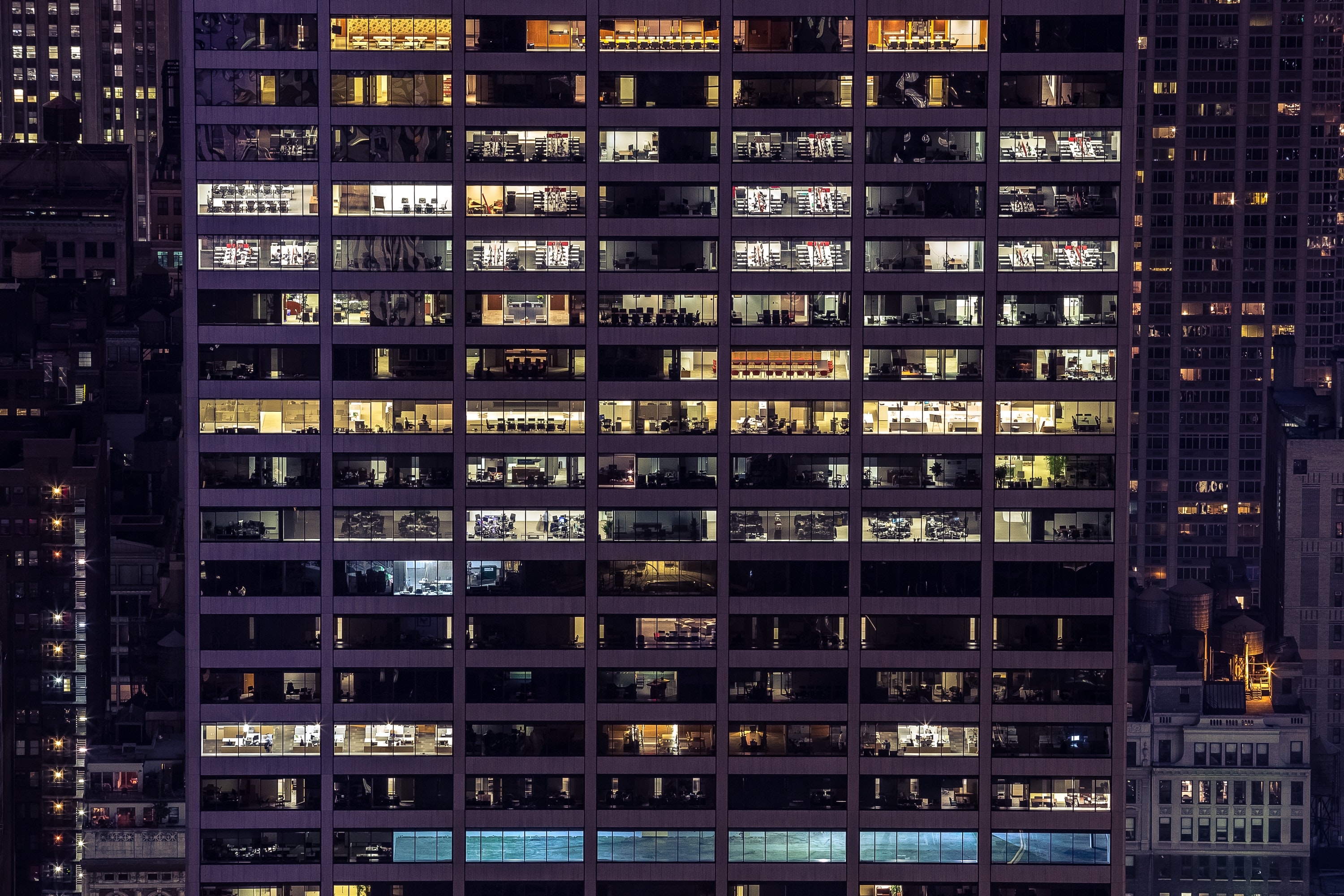 Lights in the windows of an office building in Manhattan in the evening
