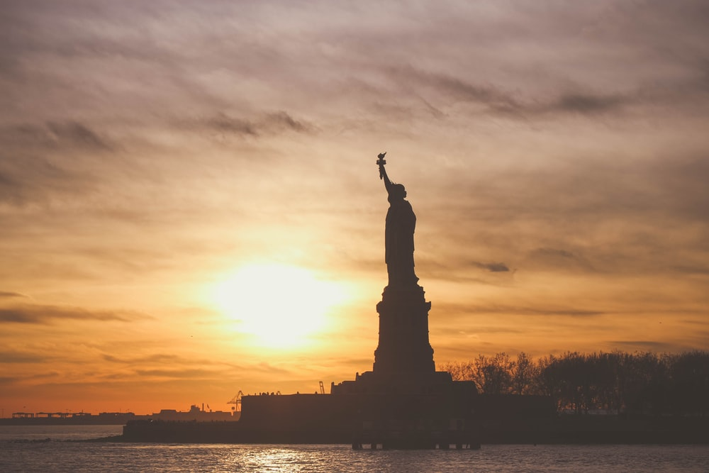 silhouette photo of Statue of Liberty during golden hour
