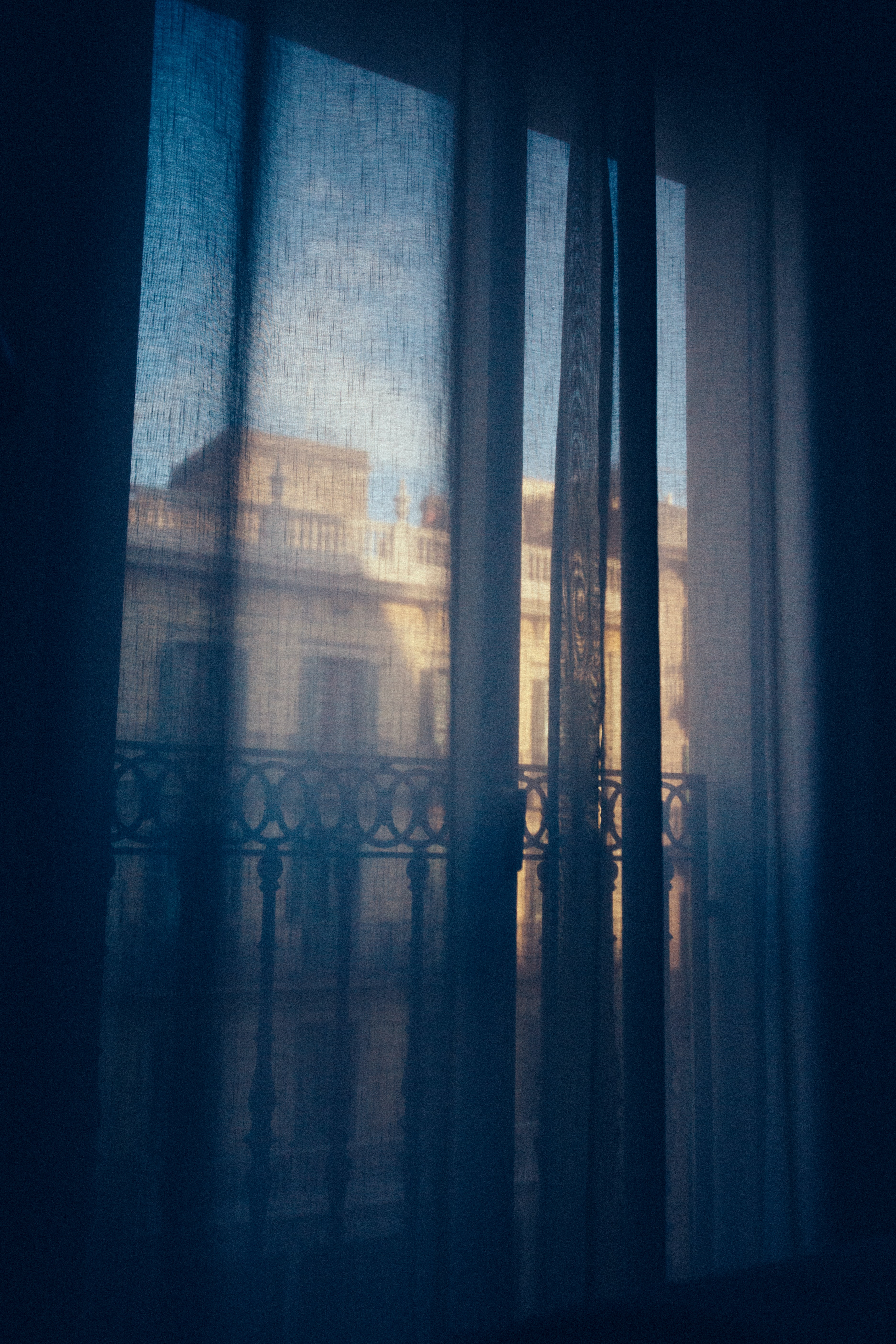 The view outside a window through a blue curtain.
