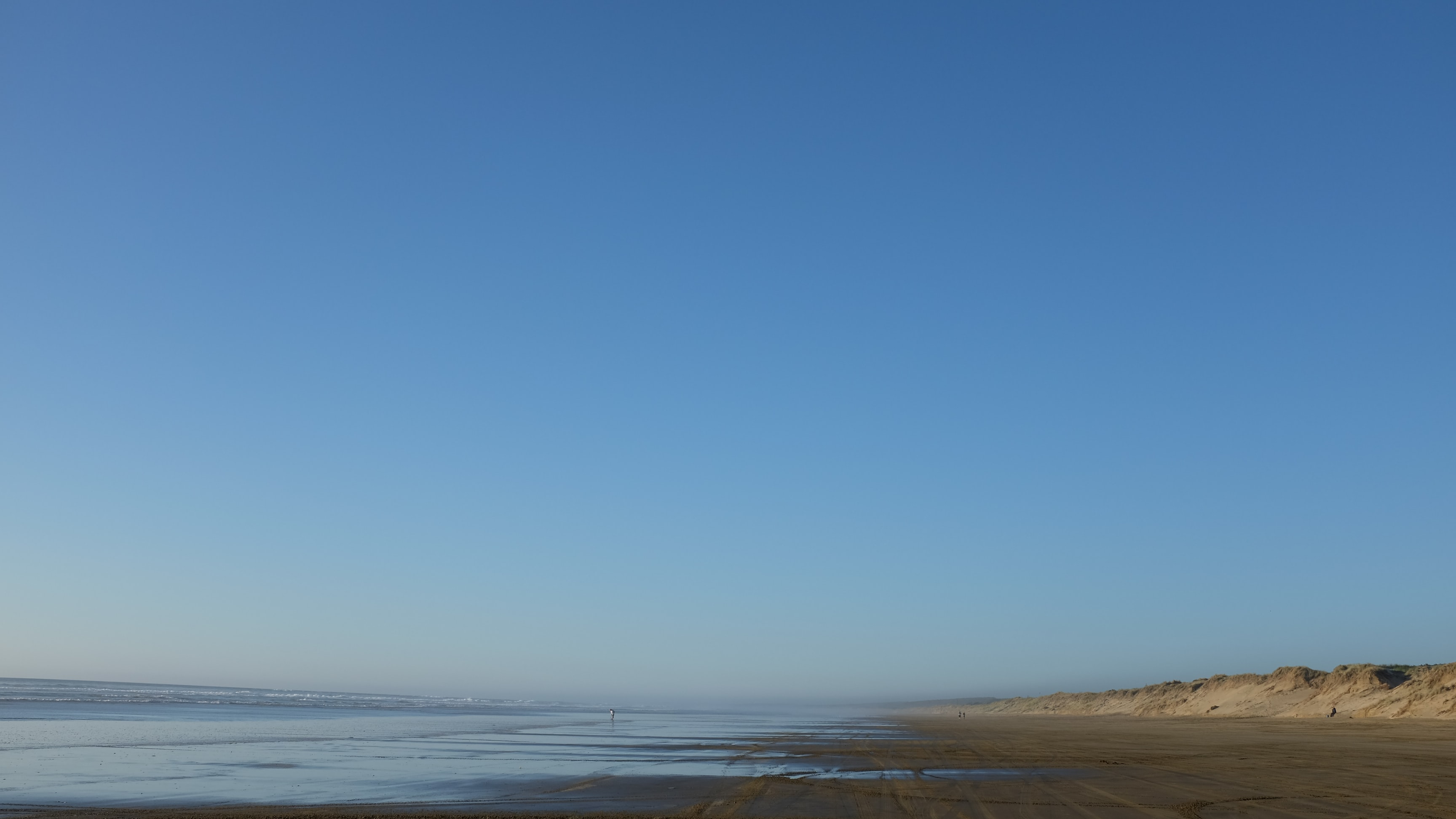 body of water and gray seashore under blue sky