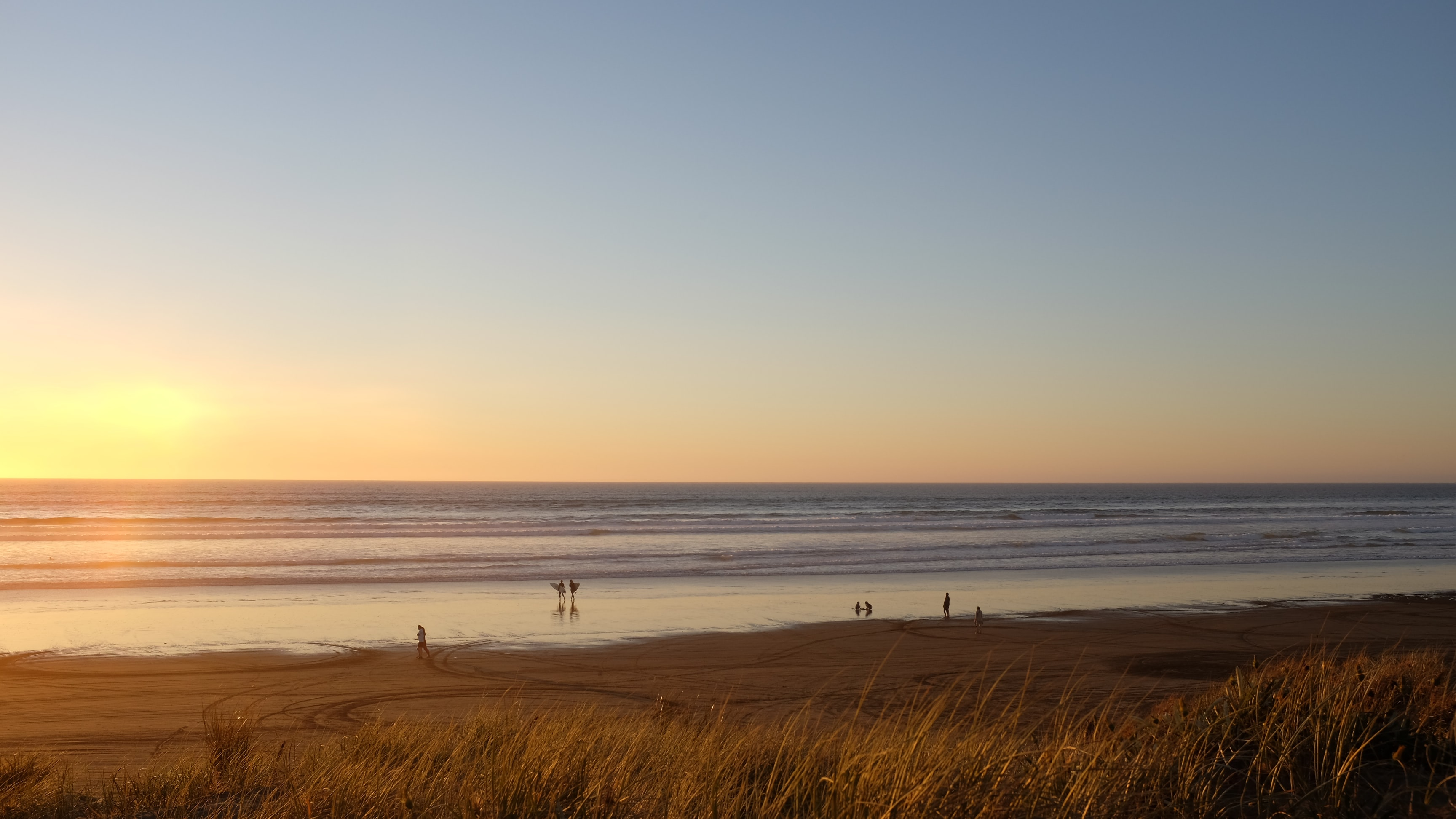 View of the calm ocean horizon and a sandy beach during sunset at Ninety Mile Beach