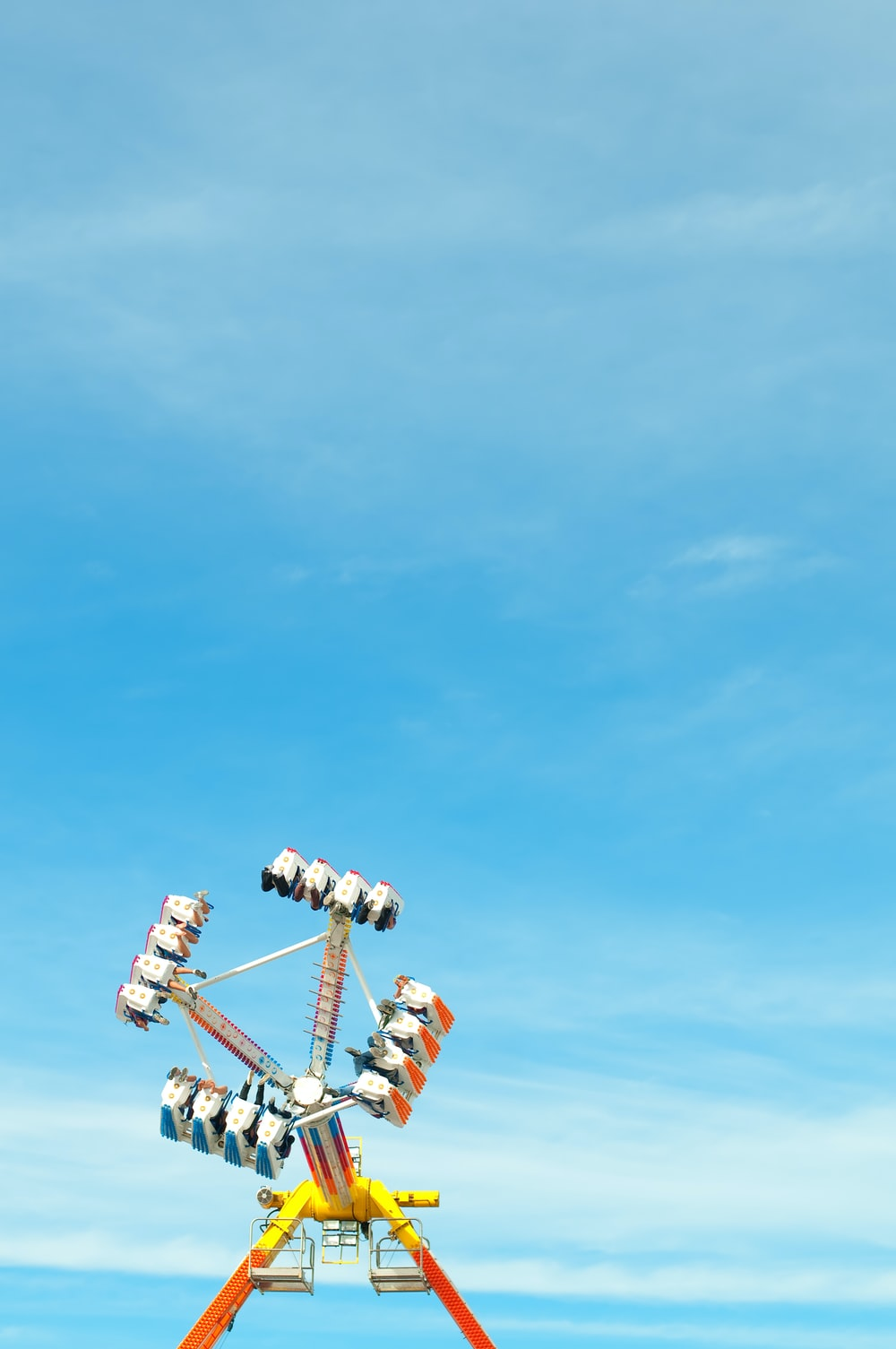 photo of yellow, orange, and blue amusement park ride under clear blue sky