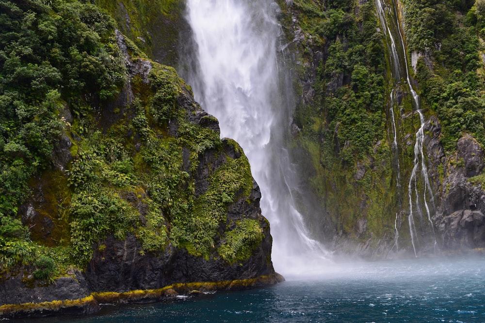 waterfall streaming through lake