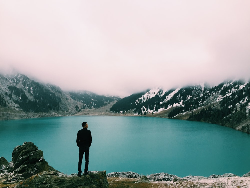man standing on mountain looking at lake under white clouds at daytime