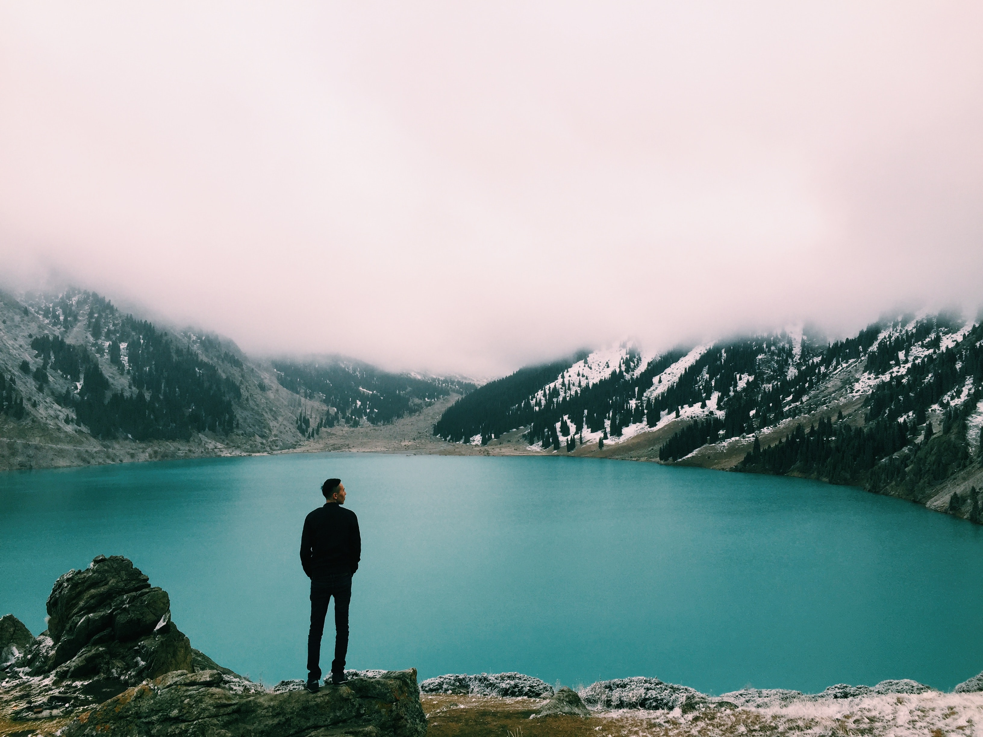 Man on a rocky ledge, looking at misty mountains and a lake, in winter, at Almaty