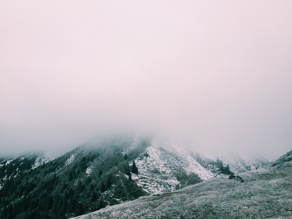 mountain range covered with snow and clouds