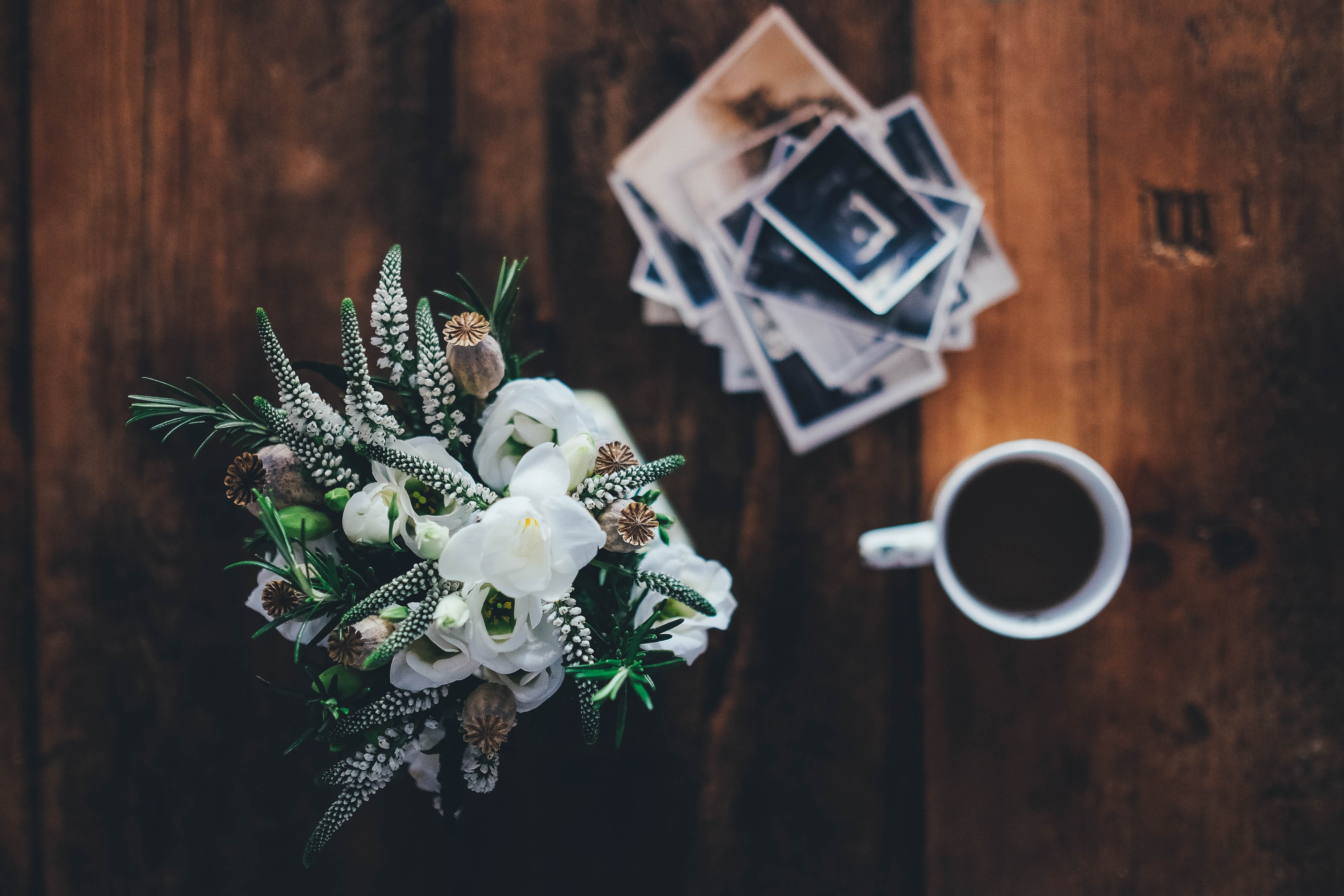 An overhead shot of a bouquet of flowers next to a cup of coffee and a stack of photographs