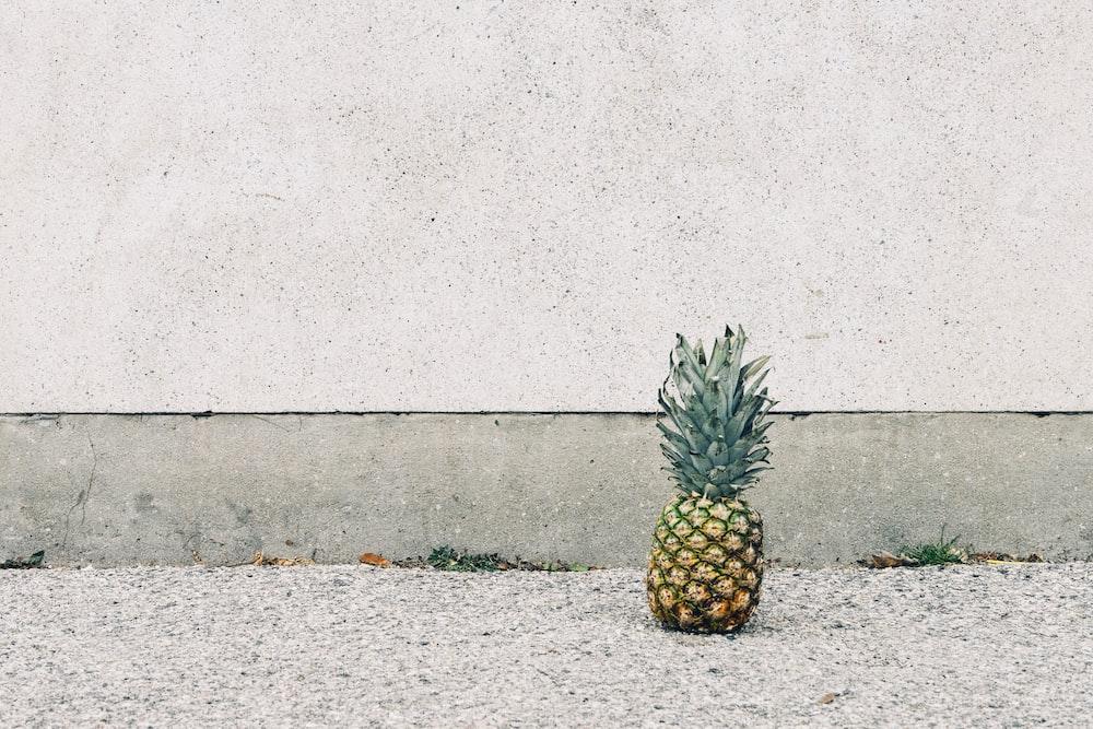 pineapple fruit beside wall