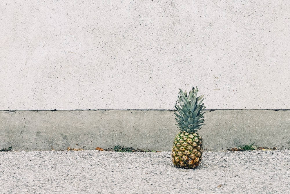 pineapple fruit beside wall