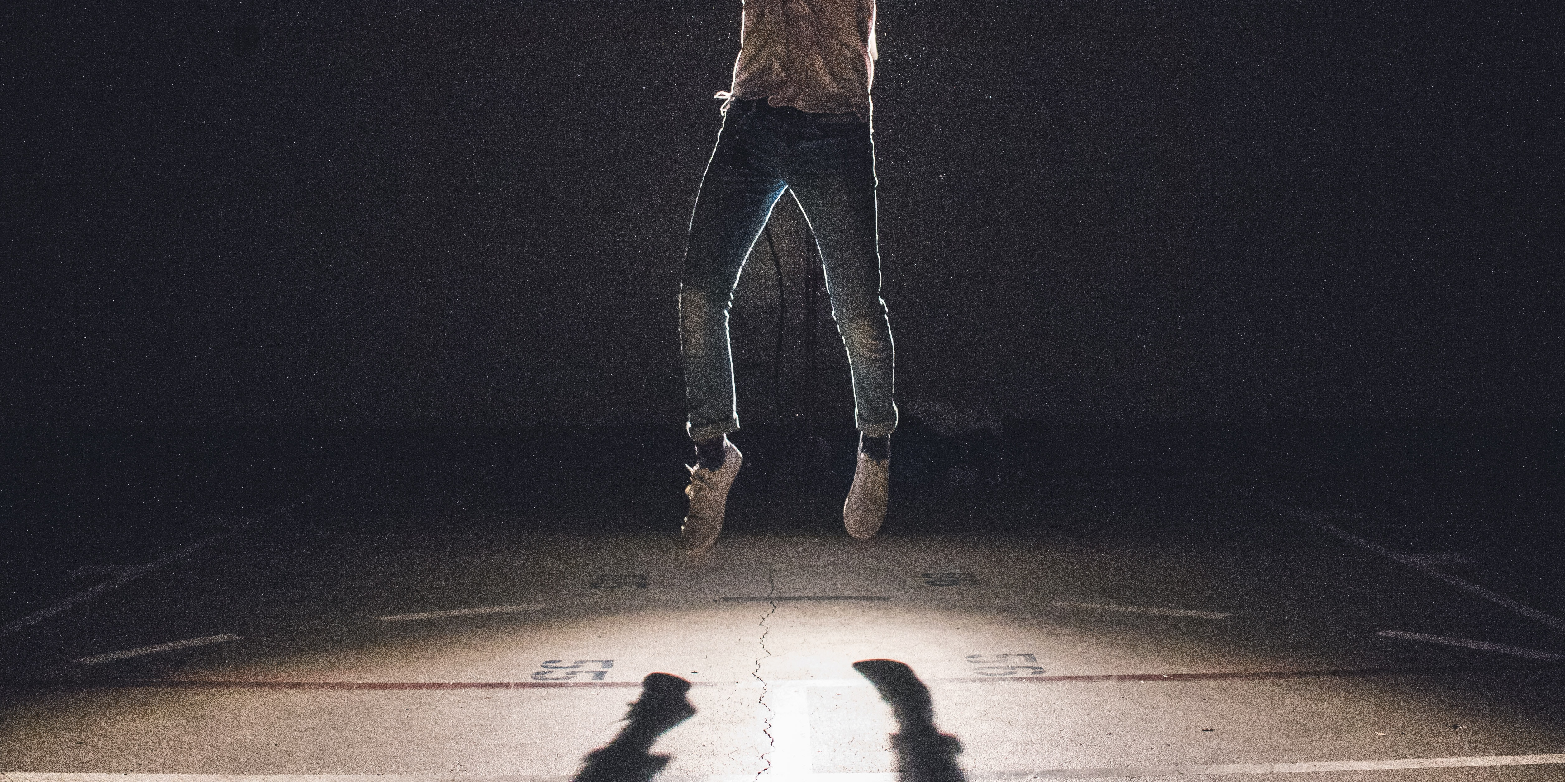 Person in jeans and sneakers jumping off of floor with shadow below