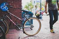 black bicycle parked beside brick wall