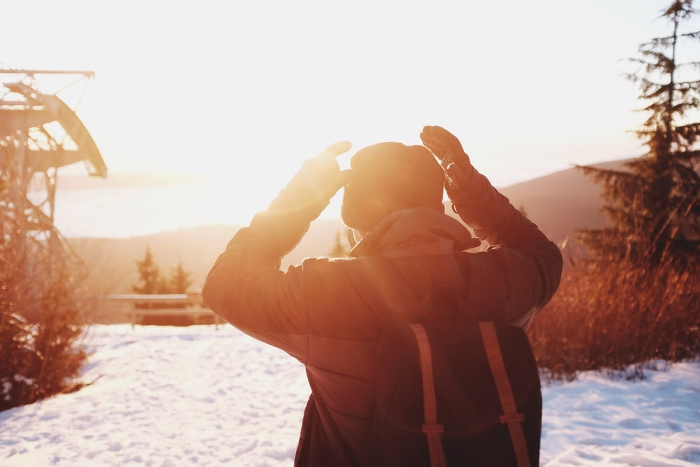 person wearing winter clothes on snow-covered hill during sunrise
