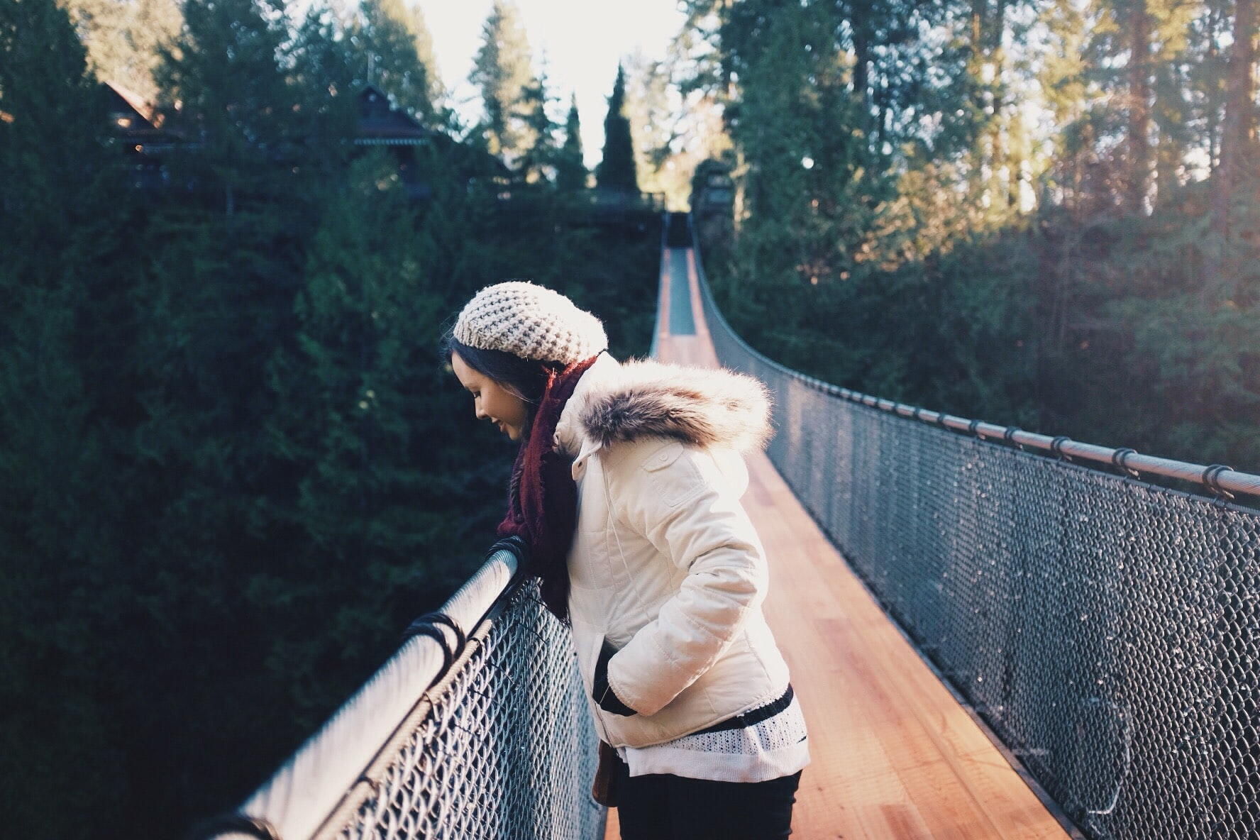 A woman in a knit cap looks over the chain-link fence on the Capilano Suspension Bridge