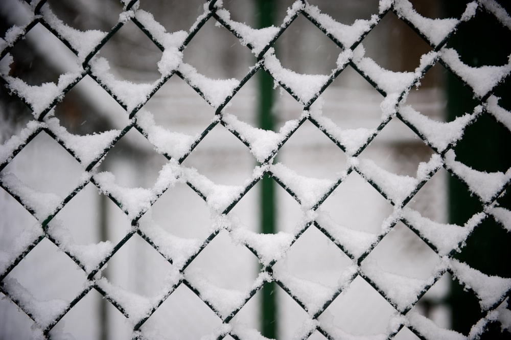 snow covered black steel fence