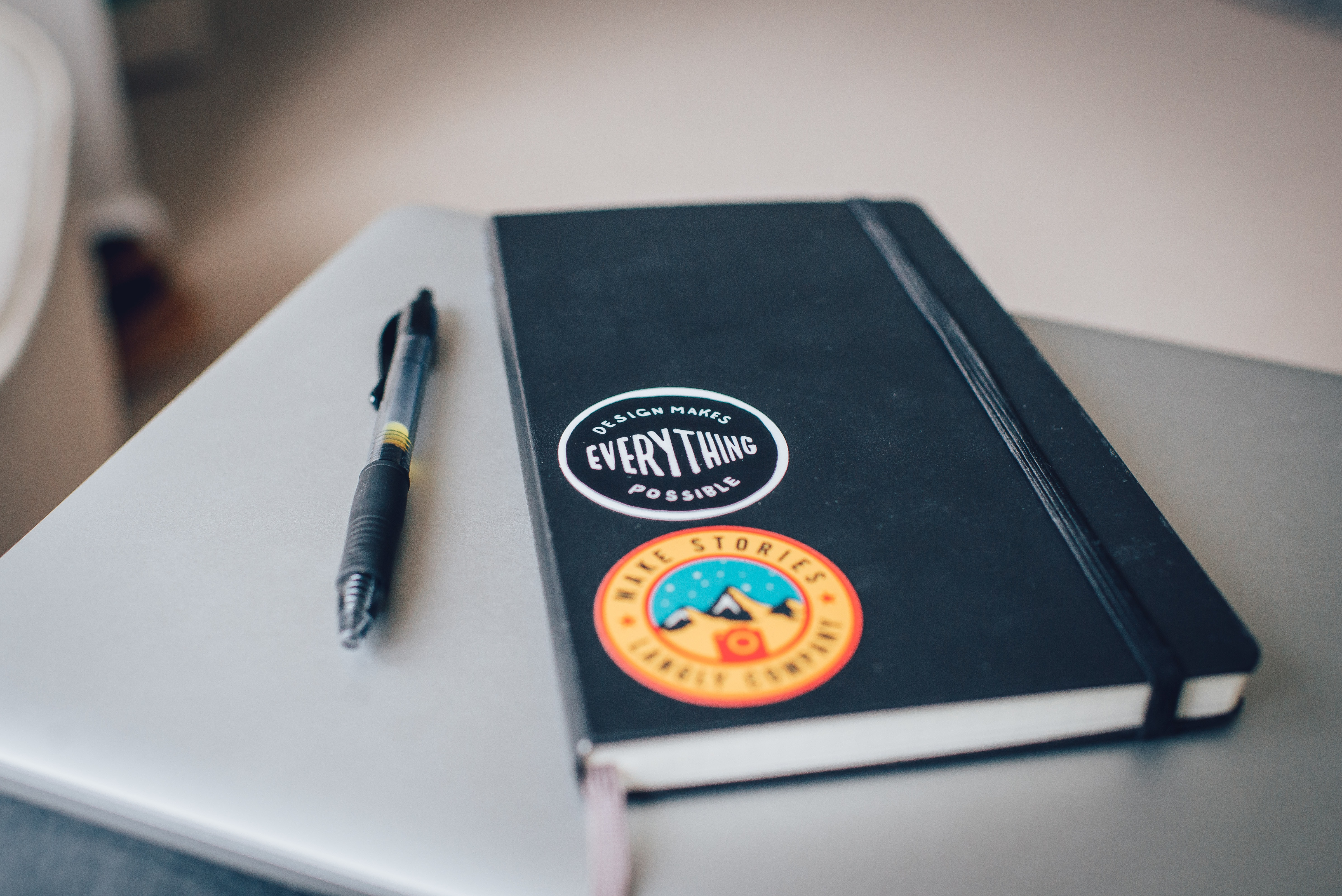 A pen next to a notebook with two stickers