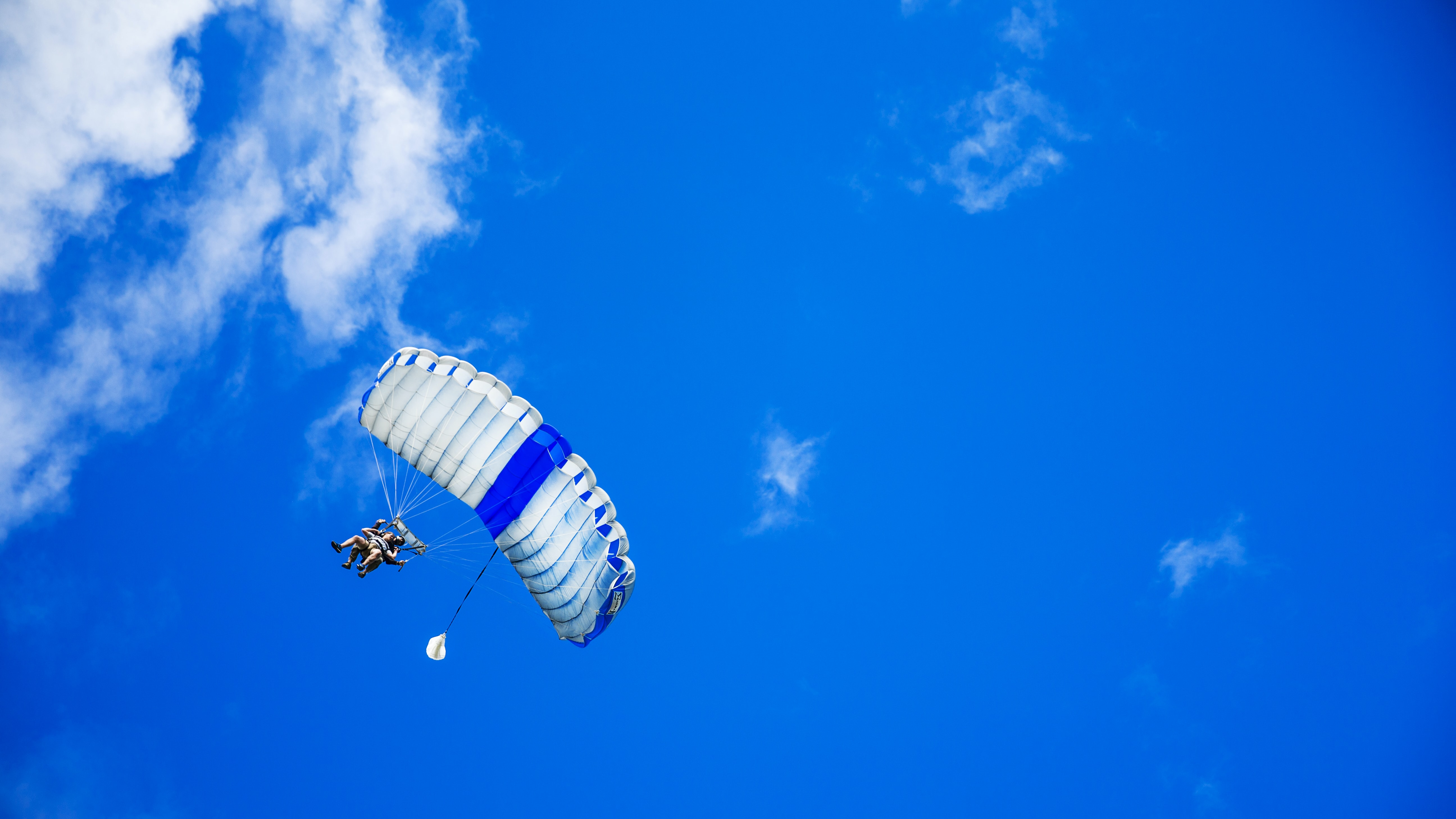 People tandem paragliding across a blue sky with soft clouds
