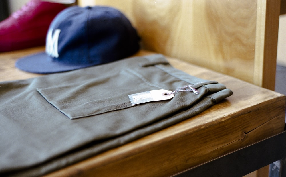 Men's hat and pants on a shelf.